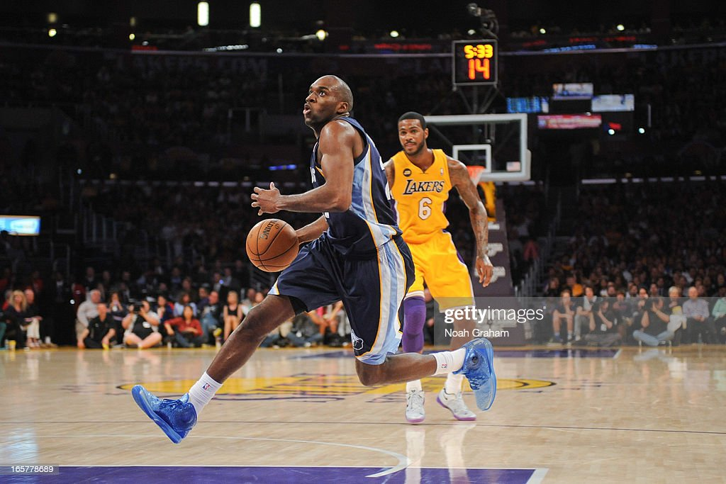 Quincy Pondexter #20 of the Memphis Grizzlies drives to the basket ahead of Earl Clark #6 of the Los Angeles Lakers at Staples Center on April 5, 2013 in Los Angeles, California.