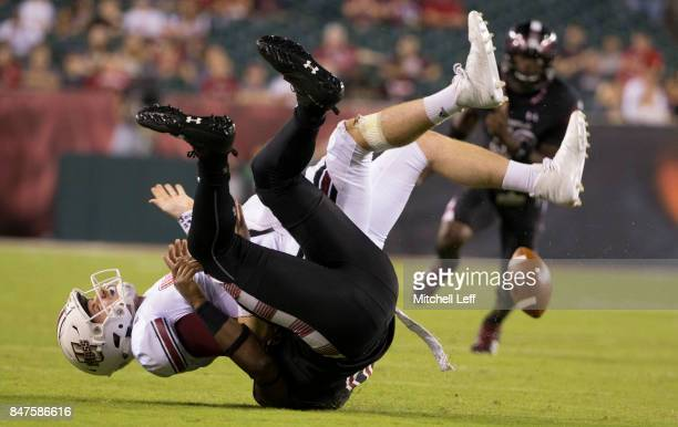 Quincy Roche of the Temple Owls sacks and forces a fumble against Andrew Ford of the Massachusetts Minutemen in the second quarter at Lincoln...