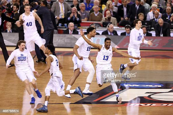 Quinn Cook Jahlil Okafor and Matt Jones of the Duke Blue Devils celebrate with teammates after defeating the Wisconsin Badgers during the NCAA Men's...