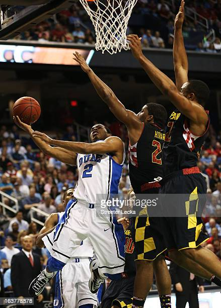 Quinn Cook of the Duke Blue Devils goes up for a shot against the defense of Pe'Shon Howard and Dez Wells of the Maryland Terrapins in the first half...