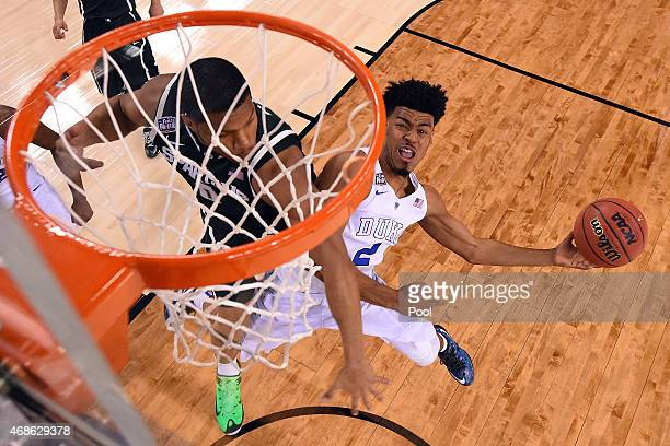 Quinn Cook of the Duke Blue Devils shoots against Marvin Clark Jr #0 of the Michigan State Spartans in the second half during the NCAA Men's Final...