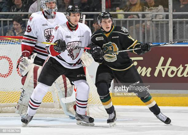 Quinn Hanna of the Guelph Storm battles against Liam Foudy of the London Knights during an OHL game at Budweiser Gardens on March 9 2017 in London...