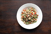 Healthy quinoa salad with chickpeas, bell peppers, cucumbers, onions and parsley.