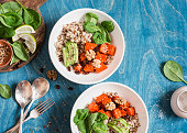 Quinoa with pumpkin, spinach and avocado. Healthy quinoa bowl. On a blue background, top view. Flat lay