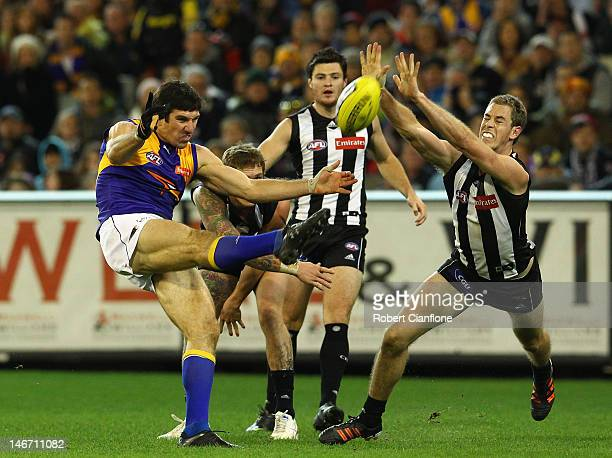 Quinten Lynch of the Eagles has his kick smothered by Nick Maxwell of the Magpies during the round 13 AFL match between the Collingwood Magpies and...