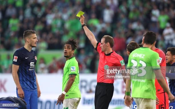 Quirin Moll of Braunschweig is booked by referee Sascha Stegemann during the Bundesliga Playoff first leg match between VfL Wolfsburg and Eintracht...