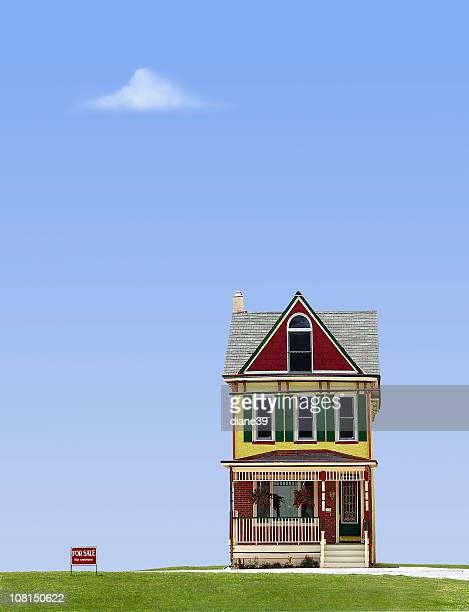 Ausgefallene Haus mit für Verkauf vor blauem Himmel