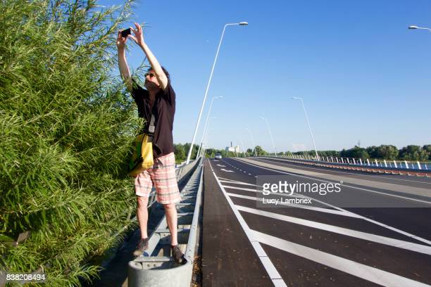 Quirky Moments: Man taking pictures next to road