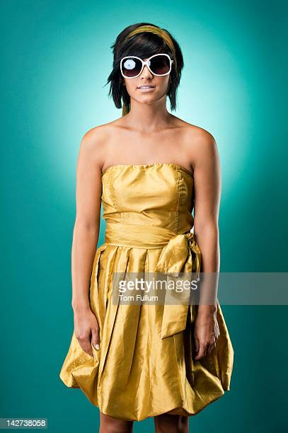 Quirky young woman in gold cocktail dress