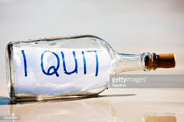 I Quit says close up message in bottle on beach