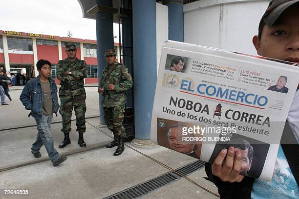 A newspaper vendor displays a newspaper depicting the two Ecuadorean presidential candidates in Quito on election day 26 November 2006 Voting was...