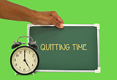 5 o'clock alarm clock quitting time chalkboard held by hand green background