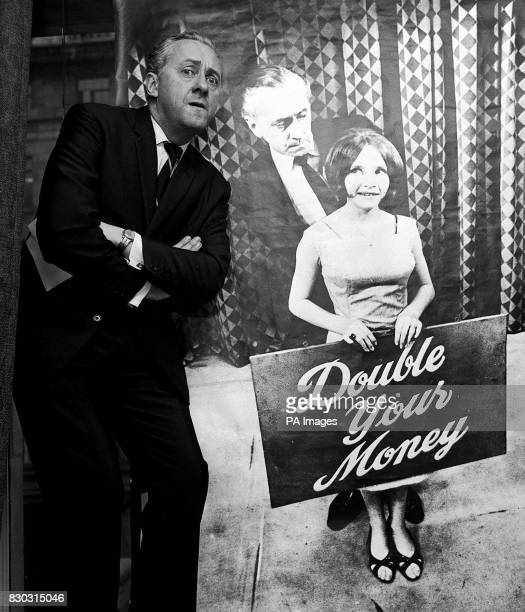 Quizmaster Hughie Green poses by a poster of himself and assistant Monica Rose in London to introduce the Travel Research Scholarship of the 'Double...