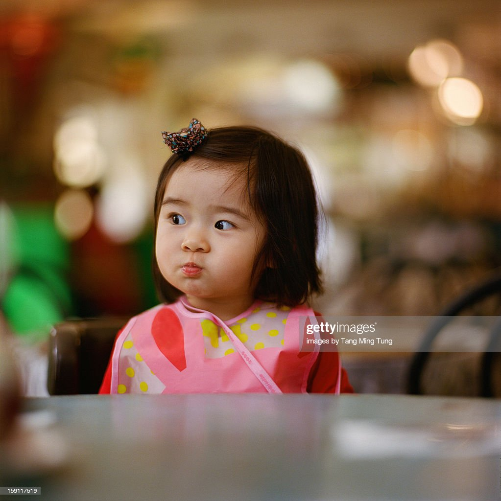 quizzical looking baby sitting on dining table : Stock Photo
