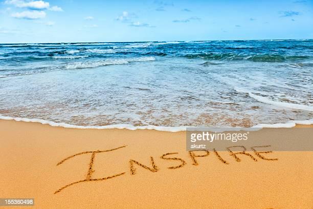 """Inspire"" written in the sand beach blue ocean"