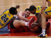 Qyntel Woods #24 of Asseco Prokom Gdynia competes with Linas Kleiza #11 of Olympiacos Piraeus and Ronnie Burrell #30 of Asseco Prokom Gdynia during...
