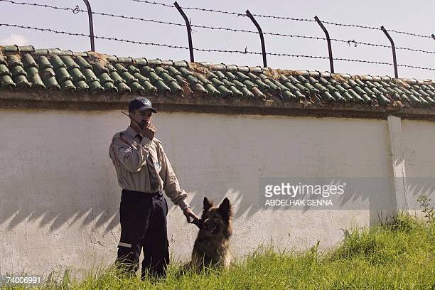 TO GO WITH AFP STORY BY SAMMY KETZ A security guard flanked by his dog speaks with a walkietalkie as he checks the area during a patrol 05 April 2007...