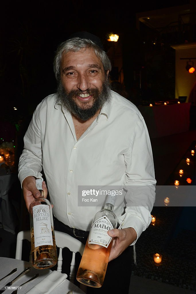 Rabbi Daniel Belaich poses with a bottle of Chateau Maime kosher pink wine during the Massimo Gargia's Party hosted by Richard Roizen at Villa Les Acanthes In Saint-Tropez on August 11, 2013 in Saint Tropez, France.
