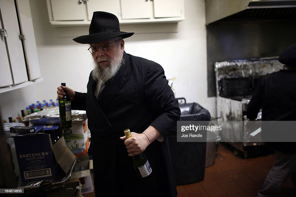 Rabbi Efraim Katz brings wine out of the kitchen for guests as he leads a community Passover Seder at Beth Israel synagogue on March 25, 2013 in Miami Beach, Florida. The community Passover Seder that served around 150 people has been held for the past 30 years and is welcome to anyone in the community that wants to commemorate the emancipation of the Israelites from slavery in ancient Egypt.