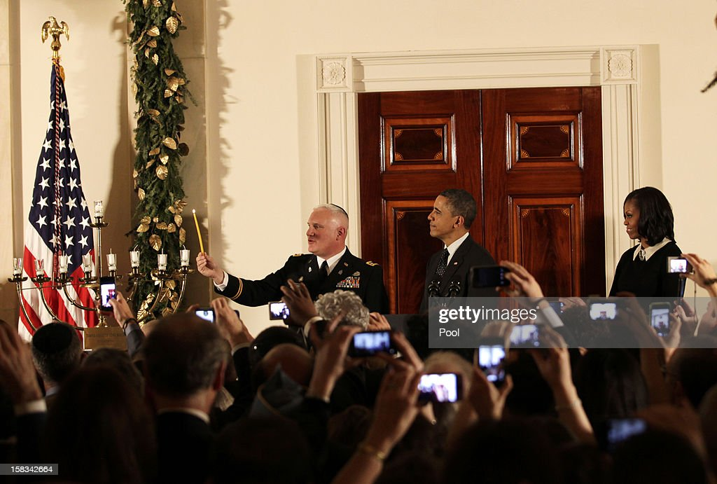Rabbi Larry Bazer lights the menorah while U.S. President <a gi-track='captionPersonalityLinkClicked' href=/galleries/search?phrase=Barack+Obama&family=editorial&specificpeople=203260 ng-click='$event.stopPropagation()'>Barack Obama</a> and first lady <a gi-track='captionPersonalityLinkClicked' href=/galleries/search?phrase=Michelle+Obama&family=editorial&specificpeople=2528864 ng-click='$event.stopPropagation()'>Michelle Obama</a> watch in the Grand Foyer of the White House December 13, 2012 in Washington DC. The celebration included the lighting of candles in a 90-year-old menorah from a temple in Long Island, New York that was heavily flooded during Superstorm Sandy.