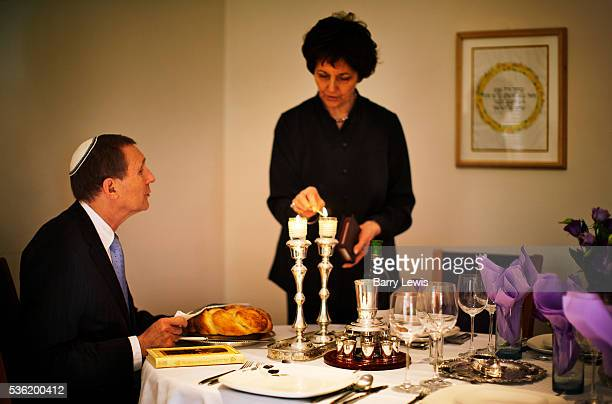 Rabbi Lionel Rosenfeld preparing for the evening Sabbat at home with his wife Natalie In front of him is the 2 plaited loaves which he coveres before...