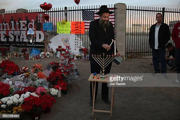 Rabbi Sholom Ber Harlig lights a menorah on the first day of Chanukah at a make shift memorial near the Inland Regional Center on December 6 2015 in...