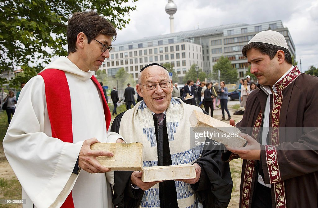Rabbi Tovia Ben-Chorin (C), Father Gregor Hohberg (L) and Imam Kadir Sanci (R) hold symbolic bricks in their hands while standing at the construction site of the future 'House of One' at Petriplatz on June 3, 2014 in Berlin, Germany. The initiative aims to bring together Jews, Christians and Muslims in one building that will house a synagogue, a church and a mosque, with a common area for exchange and discussion.