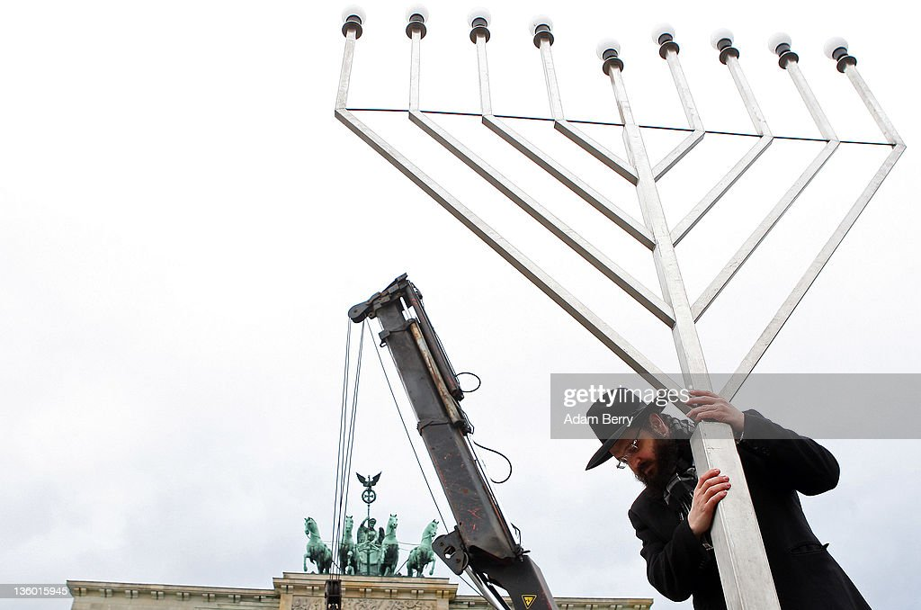Rabbi Yehuda Teichtal erects a large nine-armed candleholder, a Hannoukiah, or Menorah, ahead of the start of the eight-day-long and annual Jewish Festival of Lights known as Chanukah, in front of the Brandenburg Gate on December 20, 2011 in Berlin, Germany. The festival marks the rebellion of Maccabee Jews against the Greeks in 165 BC, which some believers say included a number of miracles pointing to divine providence.