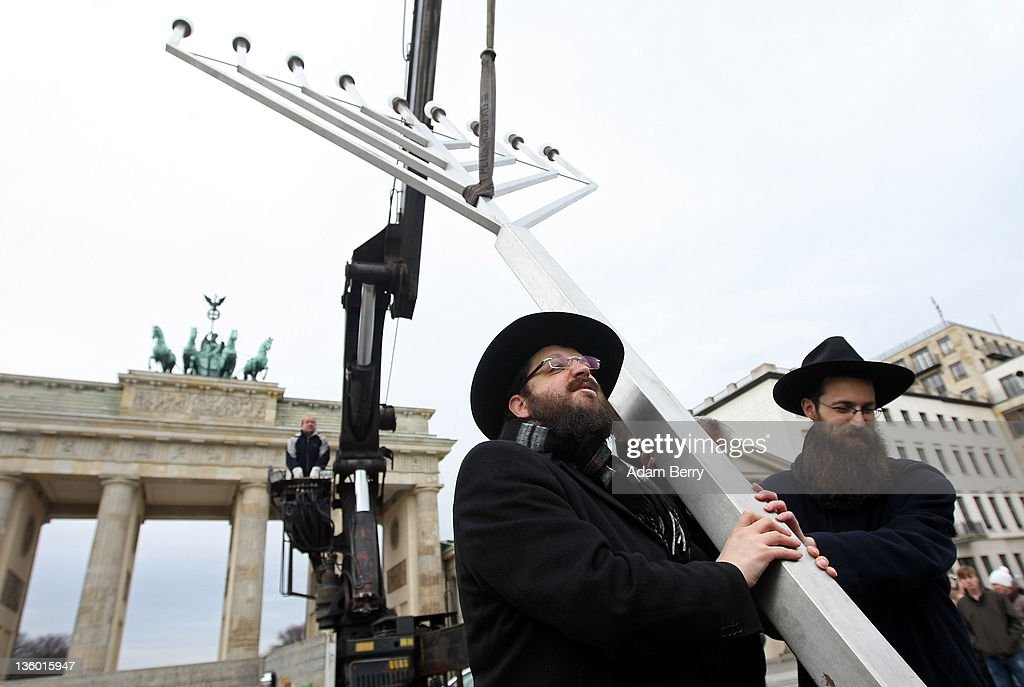 Rabbis Yehuda Teichtal (L) and Schmuel Segal erect a large nine-armed candleholder, a Hannoukiah, or Menorah, ahead of the start of the eight-day-long and annual Jewish Festival of Lights known as Chanukah, in front of the Brandenburg Gate on December 20, 2011 in Berlin, Germany. The festival marks the rebellion of Maccabee Jews against the Greeks in 165 BC, which some believers say included a number of miracles pointing to divine providence.