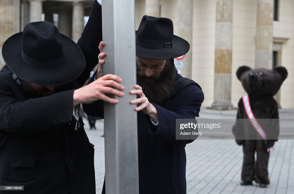 Rabbis Yehuda Teichtal (L) and Schmuel Segal erect a large nine-armed candleholder, a Hannoukiah, or Menorah, ahead of the start of the eight-day-long and annual Jewish Festival of Lights known as Chanukah, as a street performer dressed as the mascot of the city of Berlin, the Berliner Bear, looks on in front of the Brandenburg Gate on December 20, 2011 in Berlin, Germany. The festival marks the rebellion of Maccabee Jews against the Greeks in 165 BC, which some believers say included a number of miracles pointing to divine providence.