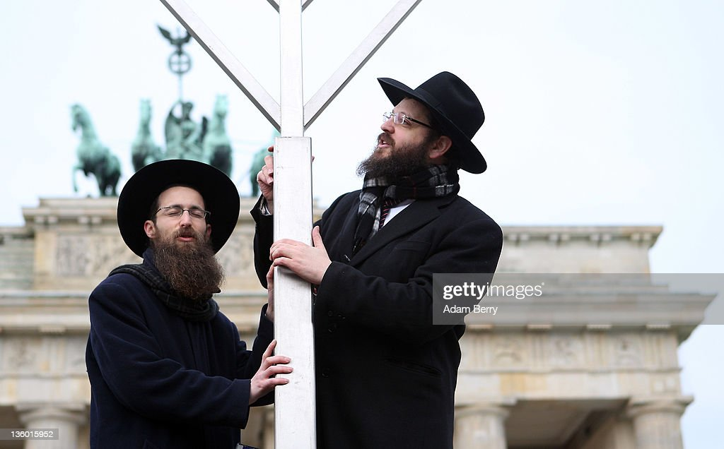 Rabbis Yehuda Teichtal (L) and Schmuel Segal pray as they erect a large nine-armed candleholder, a Hannoukiah, or Menorah, ahead of the start of the eight-day-long and annual Jewish Festival of Lights known as Chanukah, in front of the Brandenburg Gate on December 20, 2011 in Berlin, Germany. The festival marks the rebellion of Maccabee Jews against the Greeks in 165 BC, which some believers say included a number of miracles pointing to divine providence.