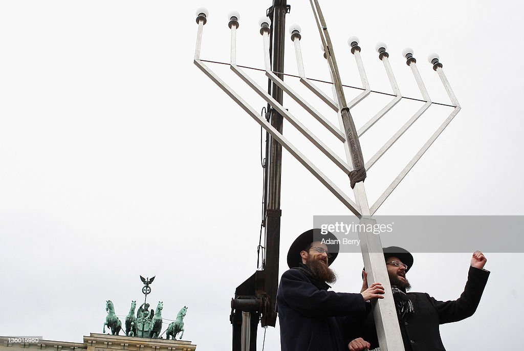 Rabbis Yehuda Teichtal (L) and Schmuel Segal sing as they erect a large nine-armed candleholder, a Hannoukiah, or Menorah, ahead of the start of the eight-day-long and annual Jewish Festival of Lights known as Chanukah, in front of the Brandenburg Gate on December 20, 2011 in Berlin, Germany. The festival marks the rebellion of Maccabee Jews against the Greeks in 165 BC, which some believers say included a number of miracles pointing to divine providence.