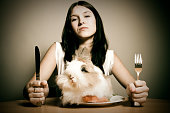 a young attractive woman getting ready to enjoy a cute fluffy bunny for dinner. yummy!