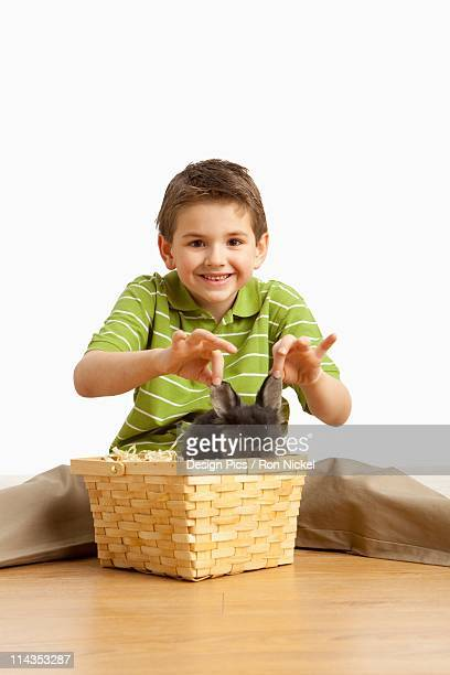 A Rabbit In A Basket And A Boy Holding It's Ears