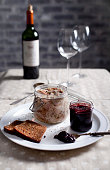 Rabbit meat in a wite wine jelly in a glass jar with bread and red grape chutney on a white plate with a bottle of wine and wine glasses on a background