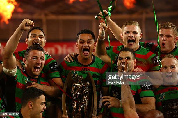 Rabbitohs captain John Sutton celebrates on the podium with his team mates after winning the 2014 NRL Grand Final match between the South Sydney...