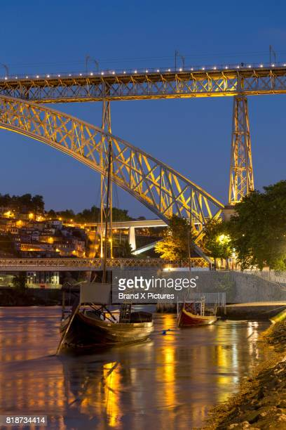 Rabelo boats and bridge in the Ribera riverside area of Porto at night
