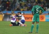 Rabiu Afolabi of Nigeria is dejected as the South Korea team celebrates after a draw gives them victory and progress to round two in the 2010 FIFA...