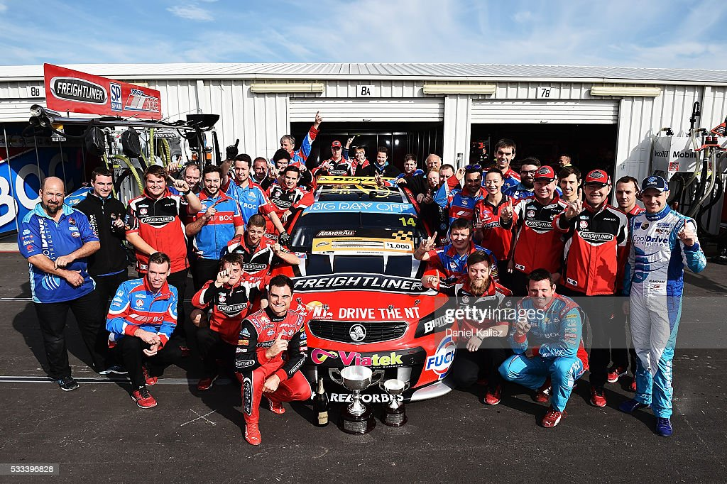 Race 1 winner Tim Slade driver of the Freightliner Racing Holden Commodore VF poses for a photo with his team prior to qualifying for race 2 of the...