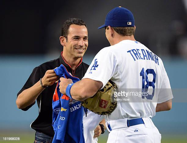 Race car driver Hélio Castroneves of Brazil swaps a shirt with Matt Treanor of the Los Angeles Dodgers after throwing out the ceremonial pitch before...