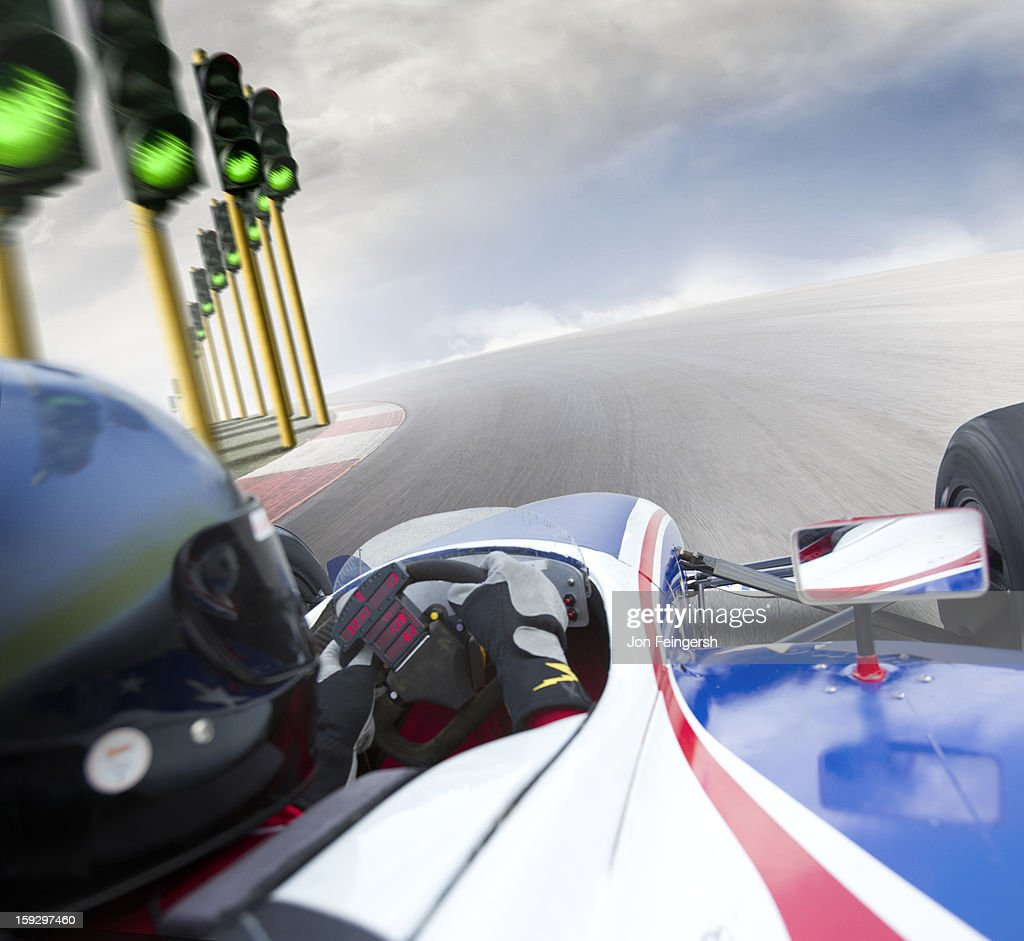 INDY race car driver in a turn with green lights. : Stock Photo