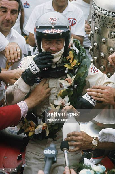 Race car driver Mario Andretti is greeted at his car with his trophy his crew and reporters after winning the Indianapolis 500 at the Indianapolis...