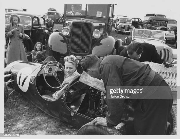 Race car driver Mrs Cook sits in her racecar in the carpark while a man inspects the back