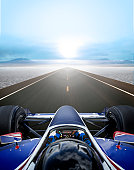 INDY race car driver on a straightaway in desert.