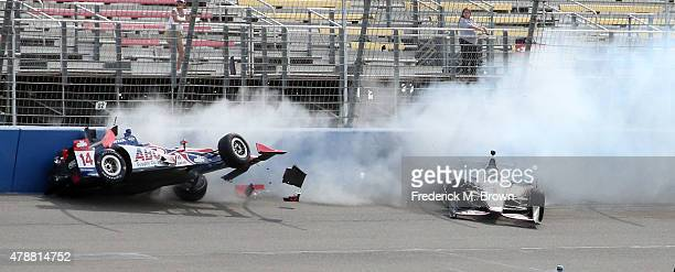Race car drivers Takuma Sato and Will Power crash during the Indy Car MAVTV 500 race at the Auto Club Speedway on June 27 2015 in Fontana California
