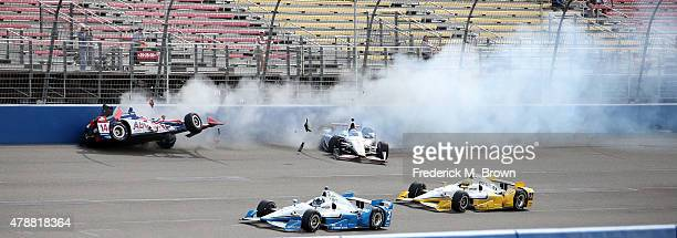 Race car drivers Takuma Sato and Will Power crash while Juan Pablo Montoya and Simon Pagenaud pass by the weckage during the Indy Car MAVTV 500 race...