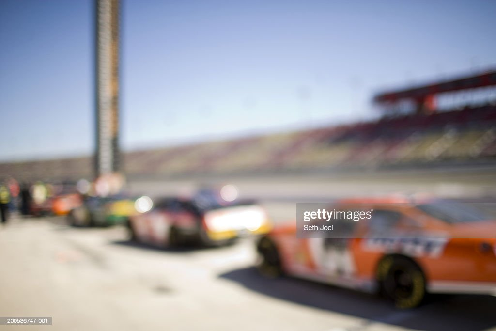 Race cars lined up in pits, (defocused)