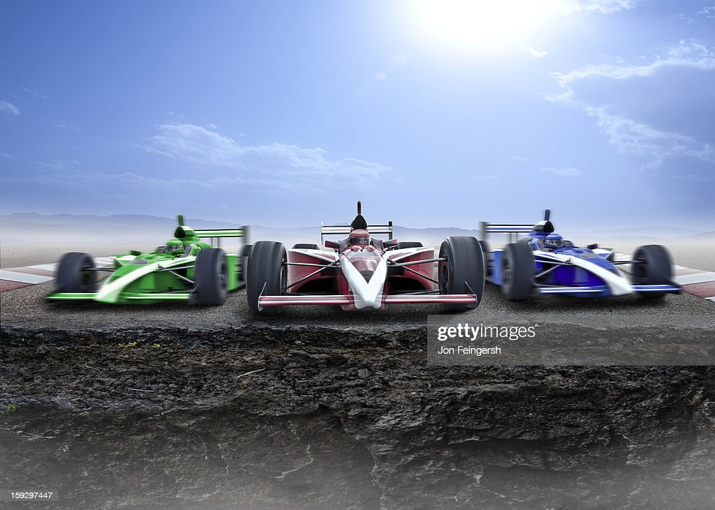 3 INDY race cars racing towards a cliff. : Stock Photo