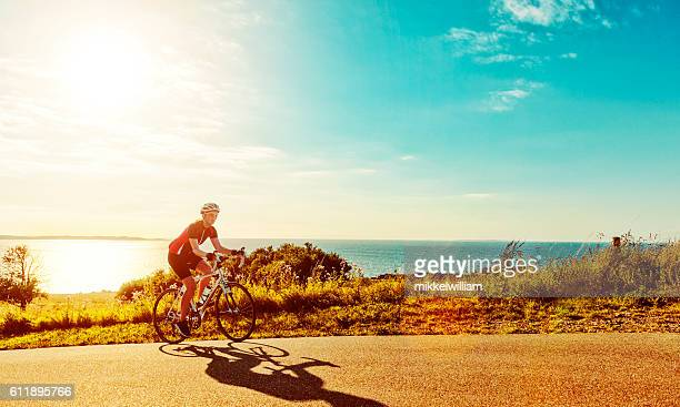 Race cyclist moves bike up steep hill at sunset