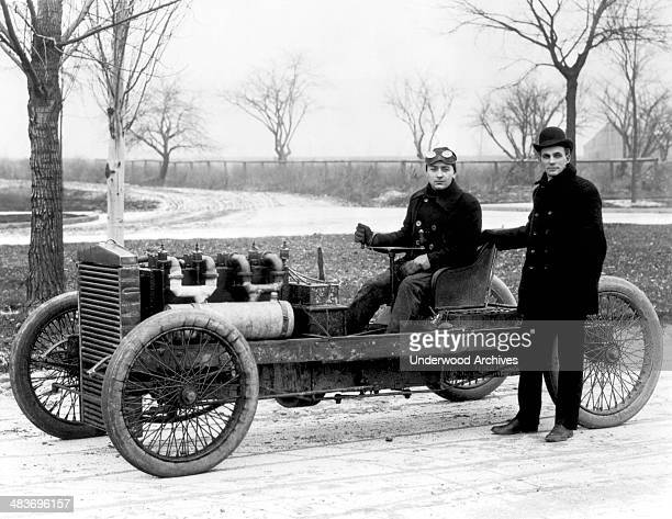 Race driver Barney Oldfield in the race car 999 that he purchased from Henry Ford standing next to him Grosse Pointe Michigan 1902